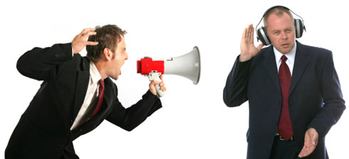 Business man with megaphone yelling at another business man with headphones on.